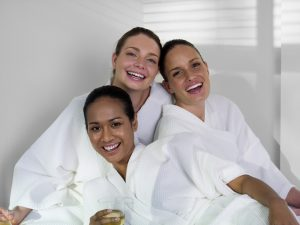 Women wearing spa robes. Friends enjoying a pamper party together.